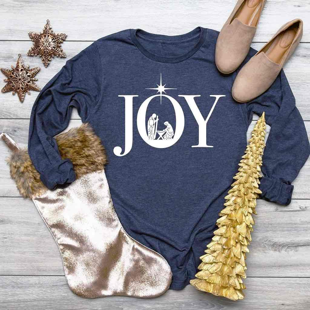 Uplifting manger scene displayed inside the word JOY printed on a premium long sleeve navy shirt