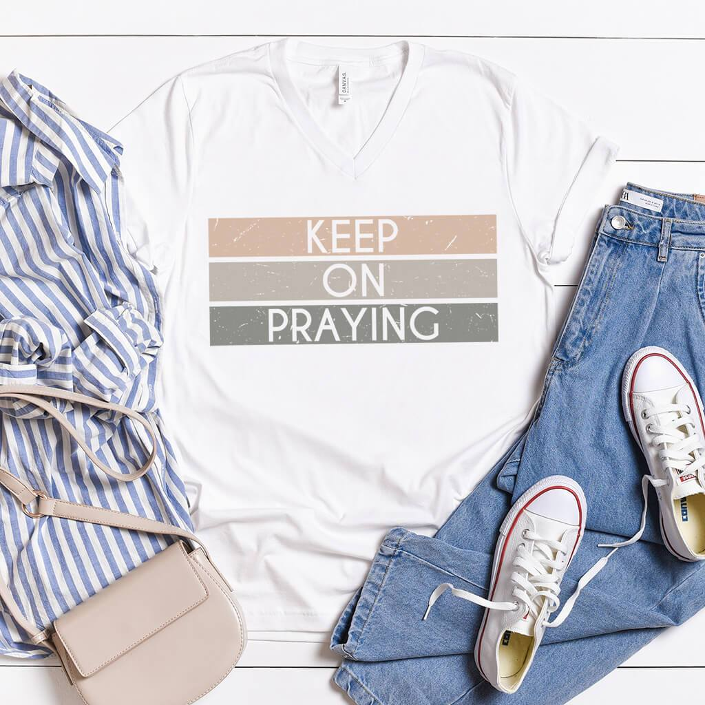 White v-neck shirt with tri-color pattern that reads keep on praying