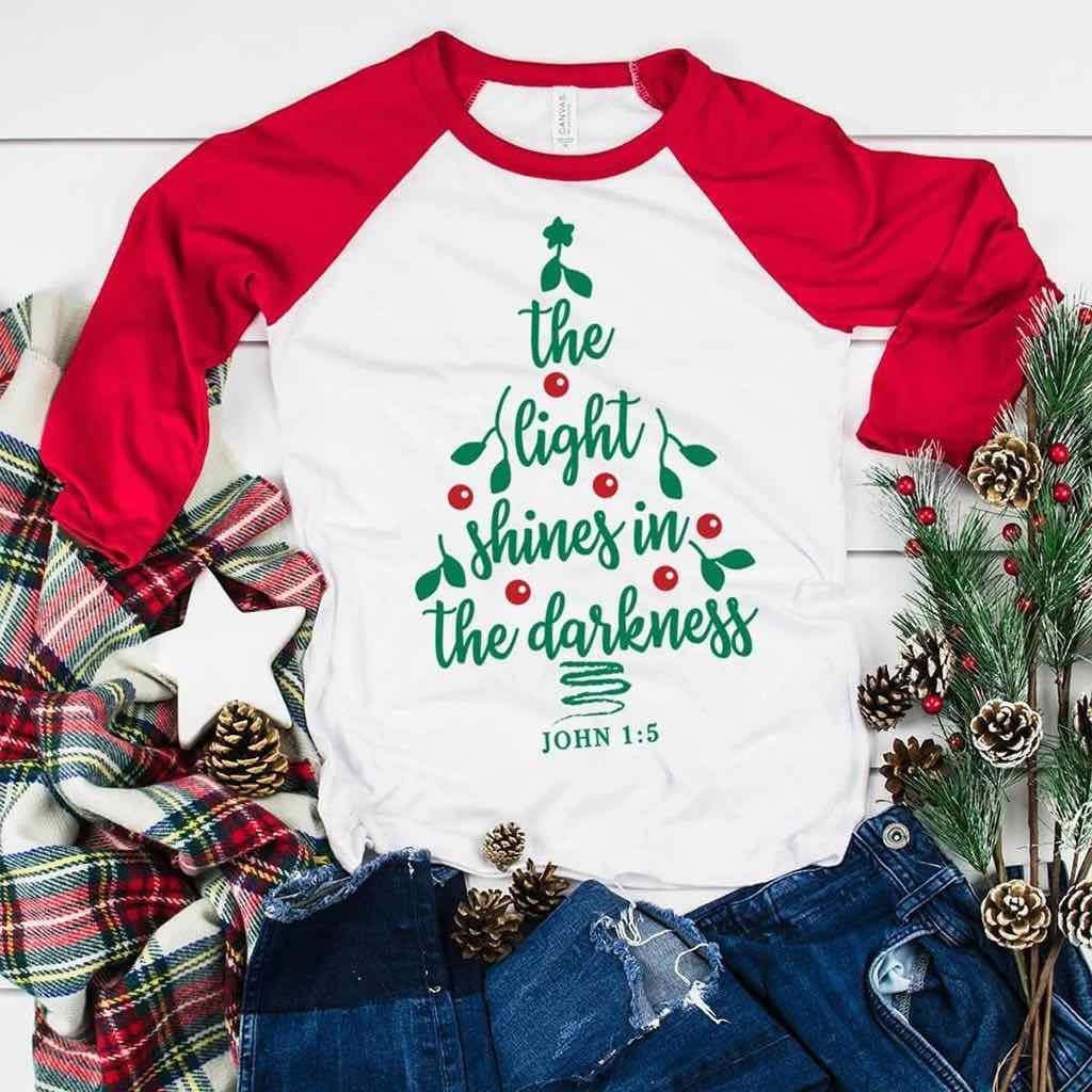 "Christmas tree design in red and green that reads ""the light shines in the darkness"" on a red and white raglan shirt"