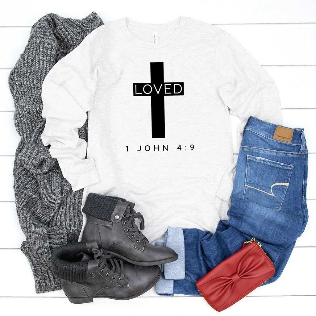 Heathered light gray long sleeve shirt that reads LOVED inside of a black cross