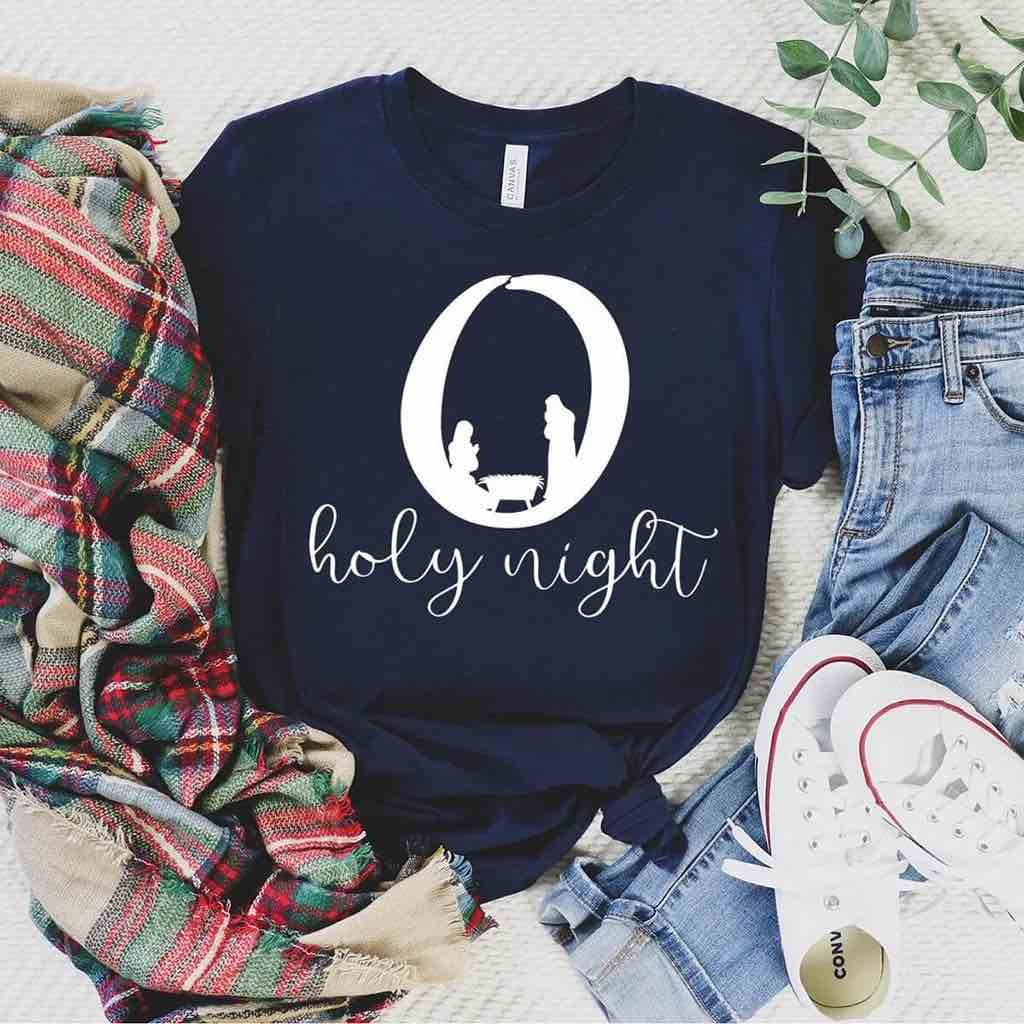 O Holy Night design contains a manger scene on this premium navy Christmas t-shirt
