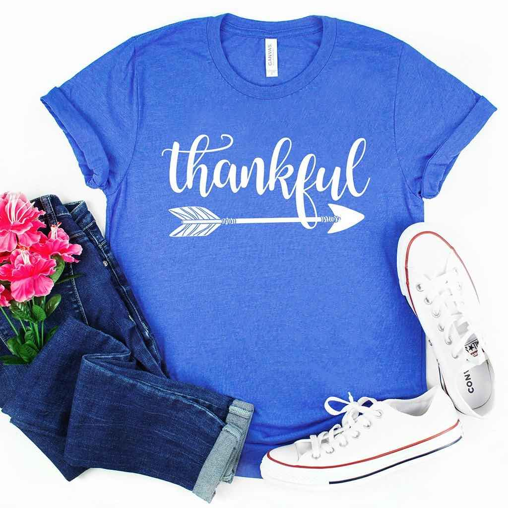 "simple white design of an arrow and ""thankful"" in ornate cursive font on a beautiful blue t-shirt"