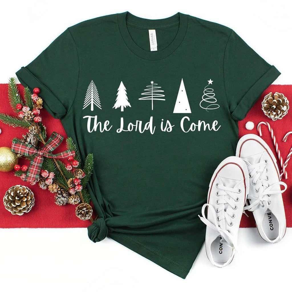 "Christmas tree design with ""the Lord is come"" written in script font on a dark green shirt"