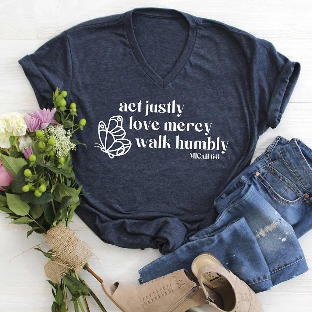 """act justly, love mercy, walk humbly"" design with a butterfly on a navy V-neck shirt"