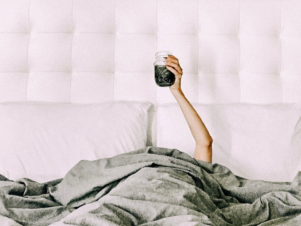 woman in bed holding up a cup of coffee in a mason jar