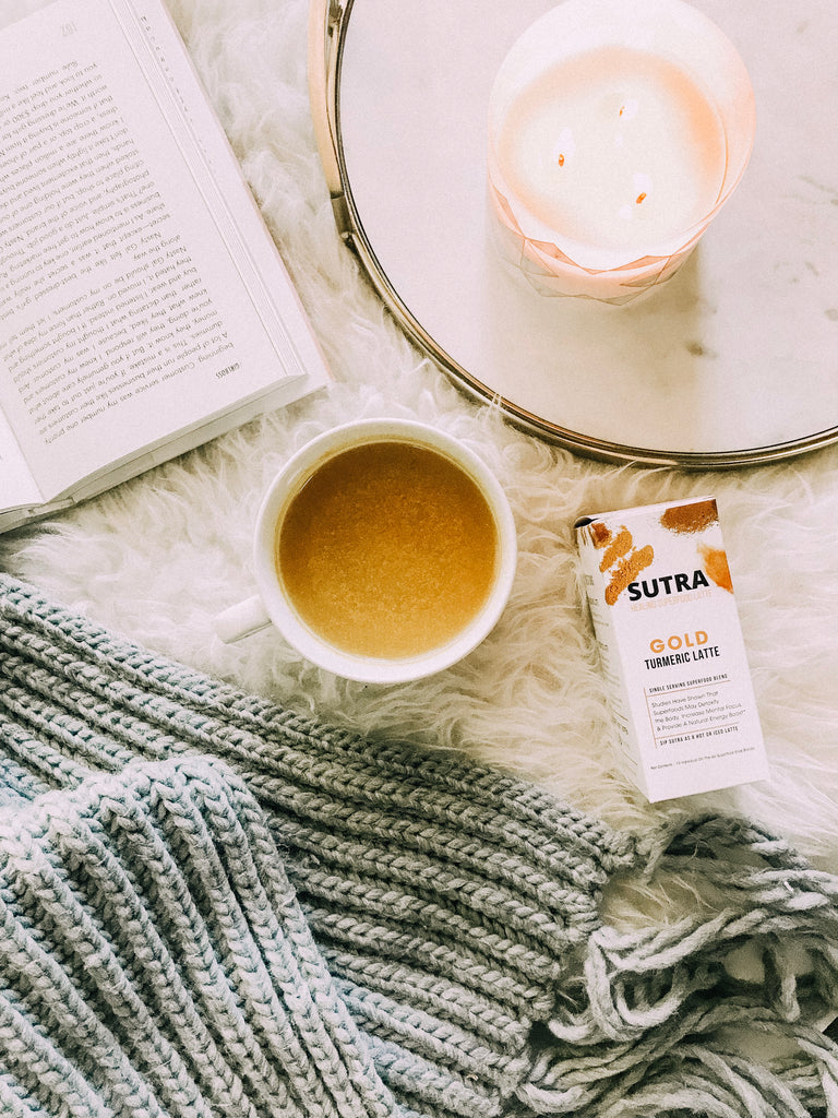 cup of coffee surrounded by a  book, a sweater, a candle, and a to-go tumeric latte