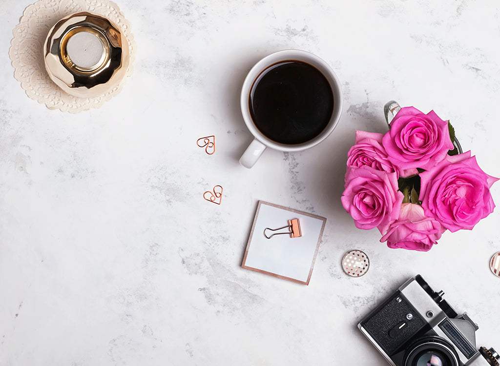 Flat lay of coffee, flowers, camera, candles and stationary items