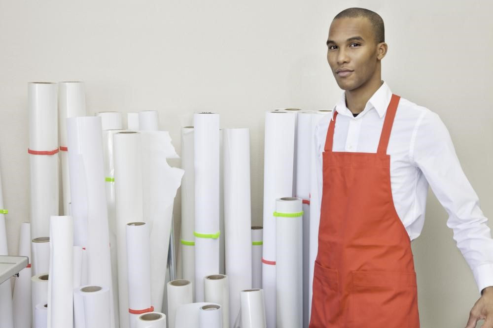 A Man Standing Next to Rolls of Printing Paper