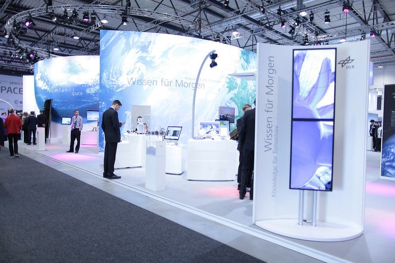 Creative and modern exhibition stand with media walls at a trade show.