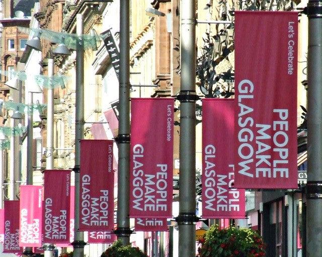 An image of fabric banners displayed on poles outside on the street.