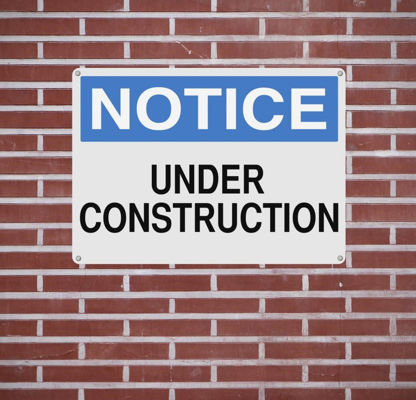 A Construction Sign Bolted on a Wall