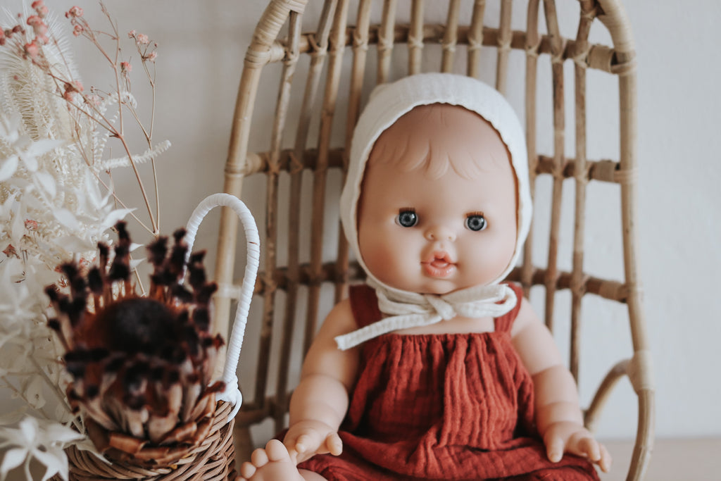 French Babydoll Caucasian Girl with Brick Romper and Ivory Bonnet