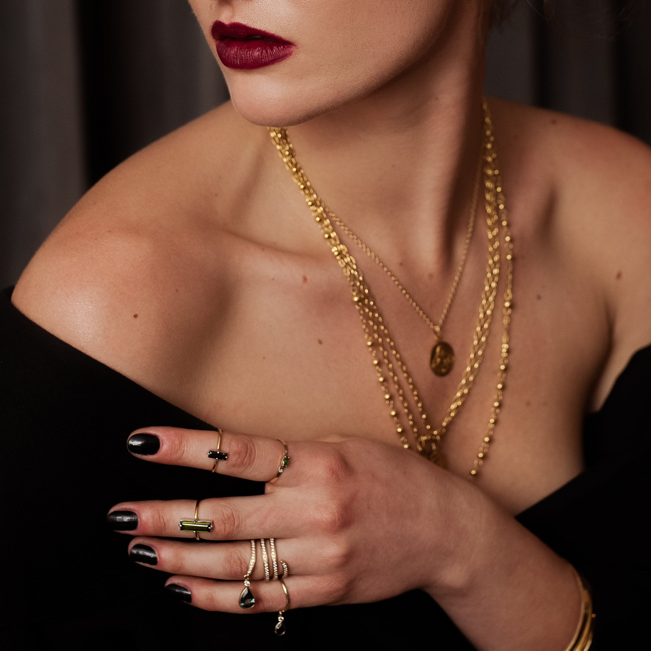 gold necklaces, gold emerald and sapphire rings, delicate rings
