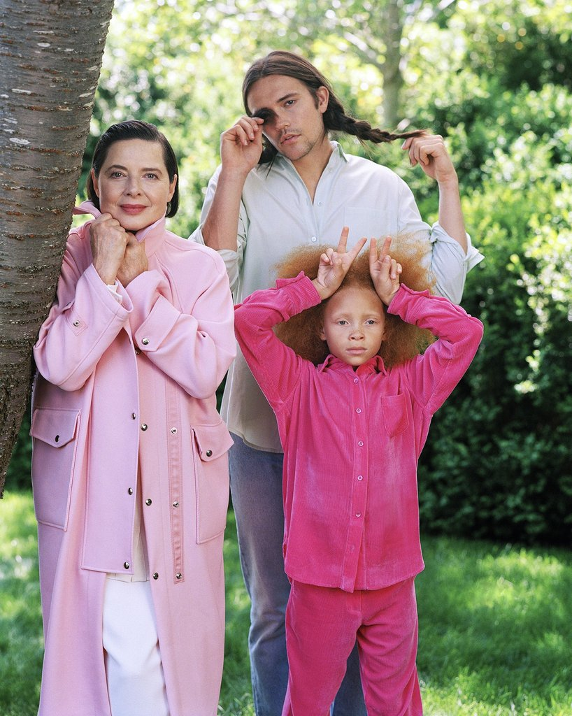 Family standing beside a tree in nature. Model wearing pink shirt and skirt hanging from tree. Sies Marjan FW '17 Campaign shot by Bruce Weber