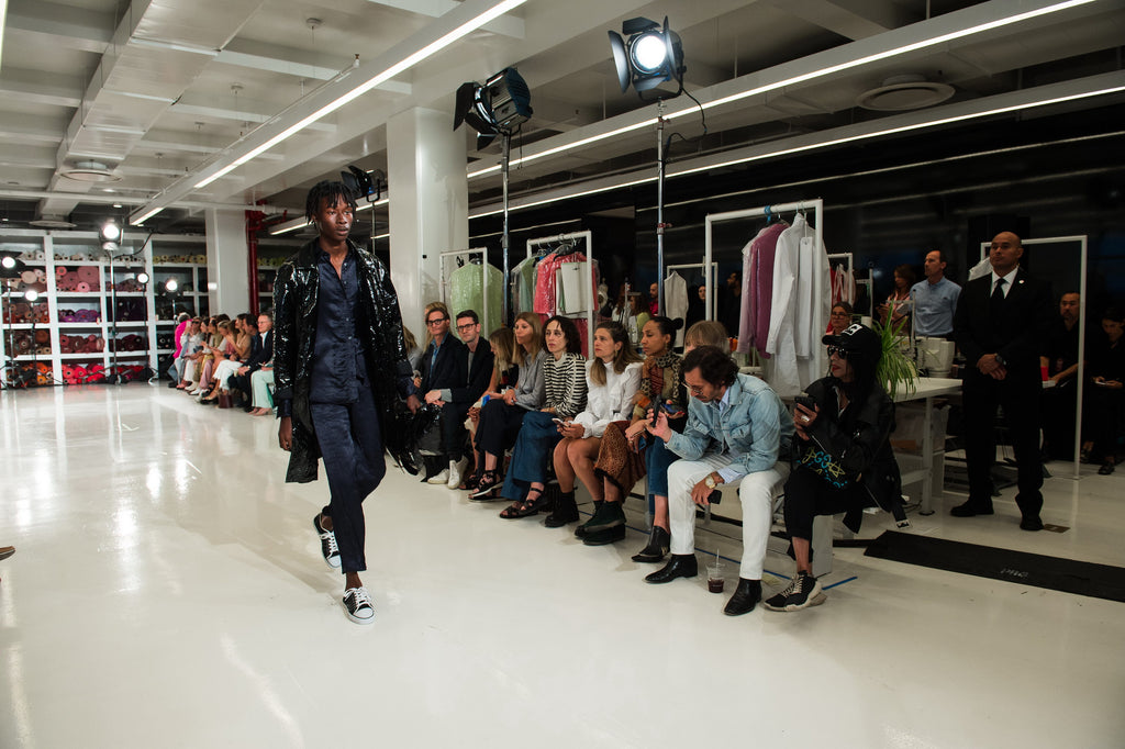 Wide angle image of male model walking in blue satin suit and black shiny coat walking the Sies Marjan  SS'18 show runway