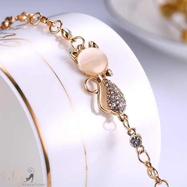 golden cat bracelet with an opal and berg crystals lying on jewelry box