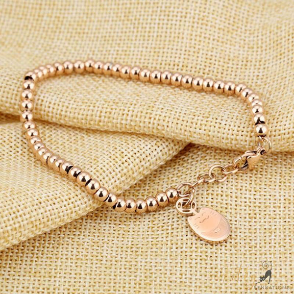 rose gold cat charm bracelet on light brown tissue