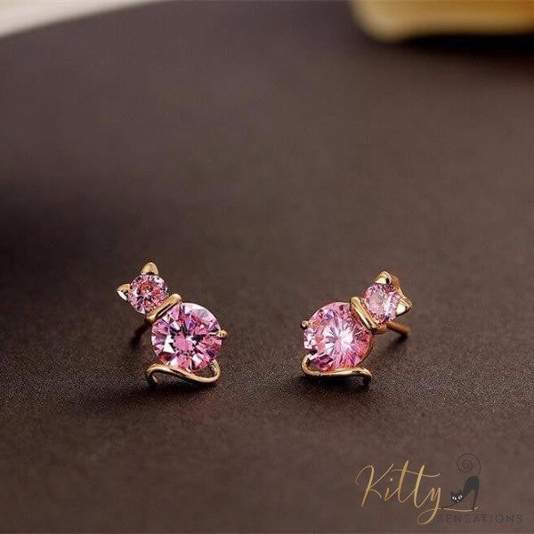 golden cat earrings with pink amethysts lying on black surace