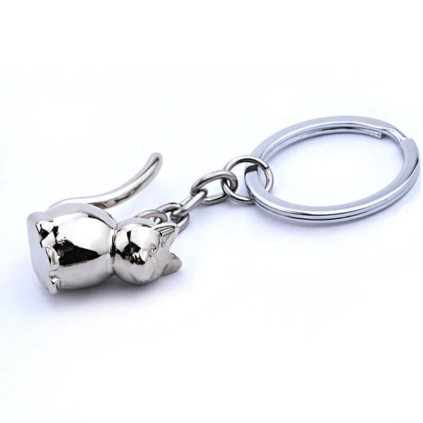 cute 3d cat keyring in sterling silver lying on white surface 27293975-silver