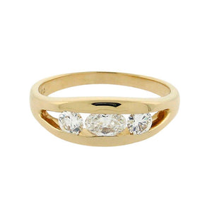 oval diamond in center with two round diamonds on the side set in a 14 k yellow gold ring