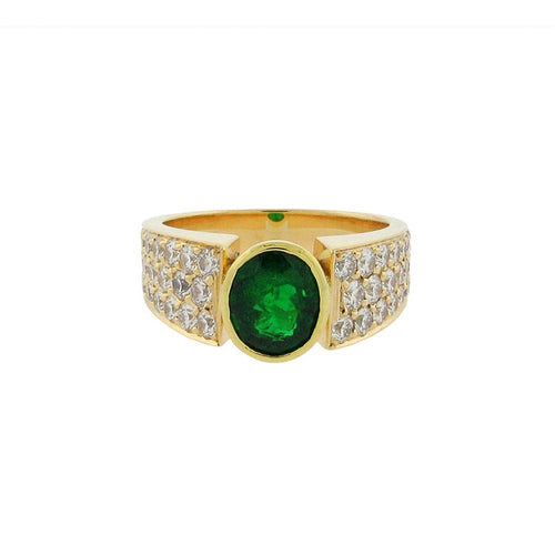 Large oval emerald with pave diamonds set in a 14 k yellow gold ring