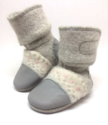 Nooks Felted Wool Booties – Narwhal. The light grey-coloured wool body of the booties has been paired with cream wool uppers and grey leather toe and heel caps for a timeless look.  The playful patterns on the uppers are hand-embroidered and add a stylish touch that makes them fancy enough for special events, and will still go well with any wardrobe for every day wear.