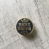 Picture of a black glitter and gold lapel pin saying black is beautiful.