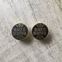 "Picture of two gold lapel pins saying ""black is beautiful"". The pin on the left is gold and black with glitter. The pin on the right is gold and black."