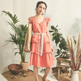 model wearing ruffle summer dress in apricot orange with belt and capped sleeves made from Lyocell | IndependentBoutique.com