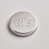 photo of stamped tin lid with the St eval logo of letters S,T and E embossed.