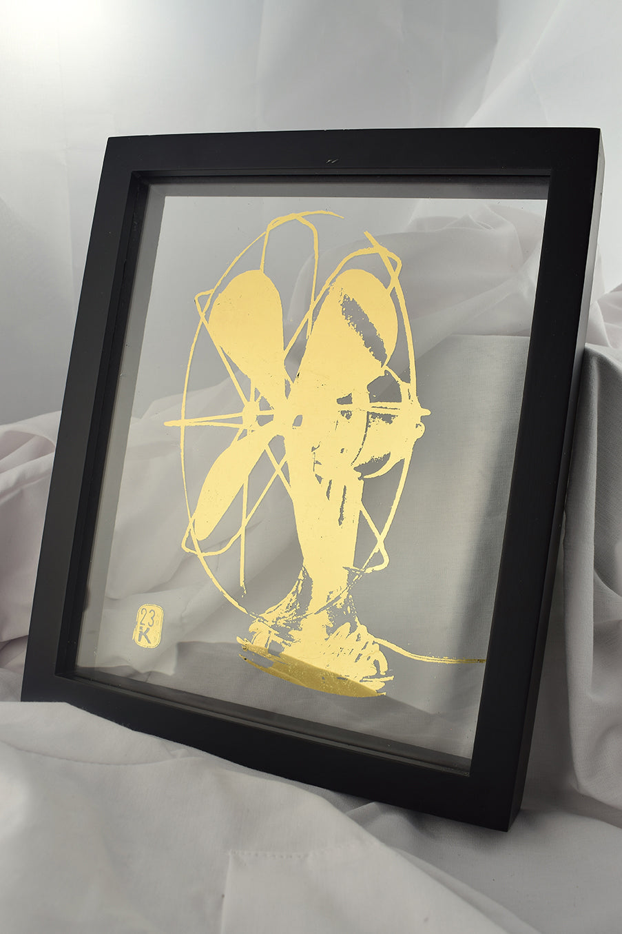 black floating frame with glass gilded with image of bauhaus fan