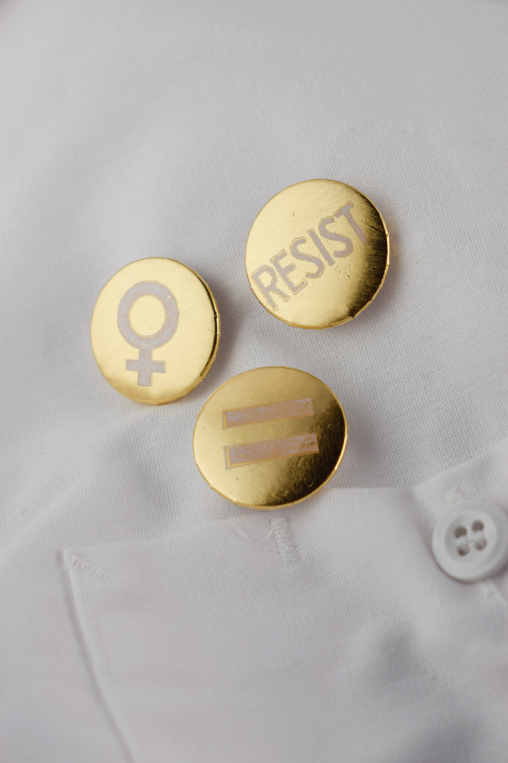 Three gold protest buttons