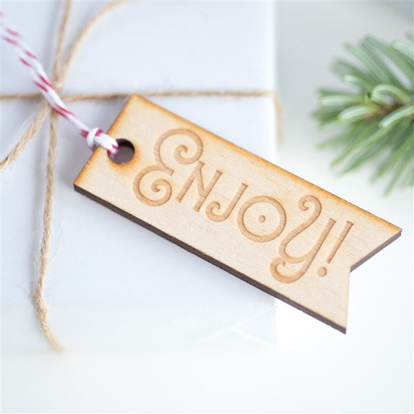 Decorative, wooden cut out tags engraved with Enjoy!. Supplied hanging from red & white baker's twine (10pk)