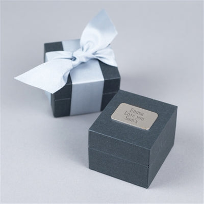 A high quality grey gift box hand-tied with a light-grey grosgrain ribbon personalised with an engraved silver nameplate