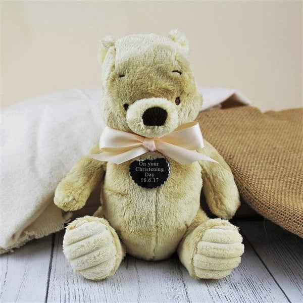 Winnie The Pooh personalised with an engraved silver polished scalloped hang tag around his little neck tied with a soft satin ribbon