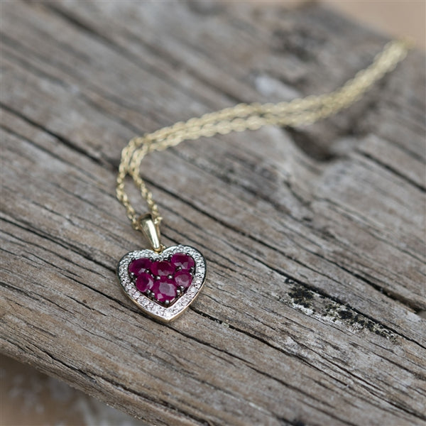 The Rubies and diamond stones are pave set into a 9K yellow gold heart pendant which hangs from a solid 9K yellow gold curb chain