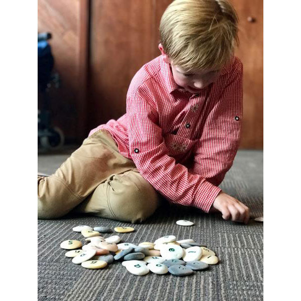 Boy plays with Alphabet Pebbles