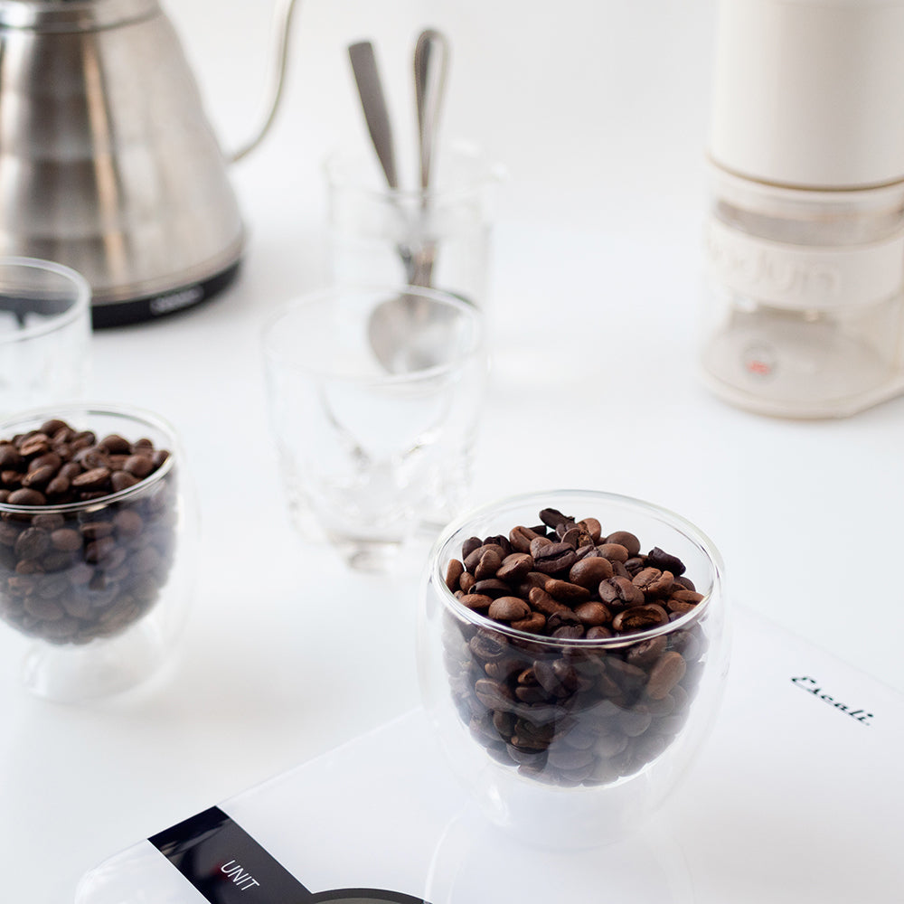 The basic equipment needed to cup coffee: a kettle, weighing scale, burr grinder, a few soup/cupping spoons, two to five vessels of the same size, a dip cup full of hot water, and two to five different coffees to cup.