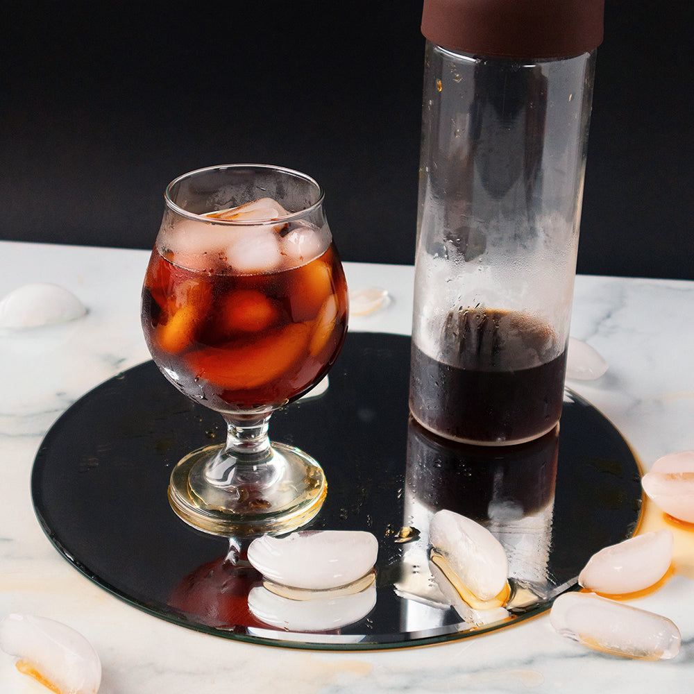 A glass of iced cold brew, a cold brew bottle, and several ice cubes sit on a circular mirror on a granite countertop.