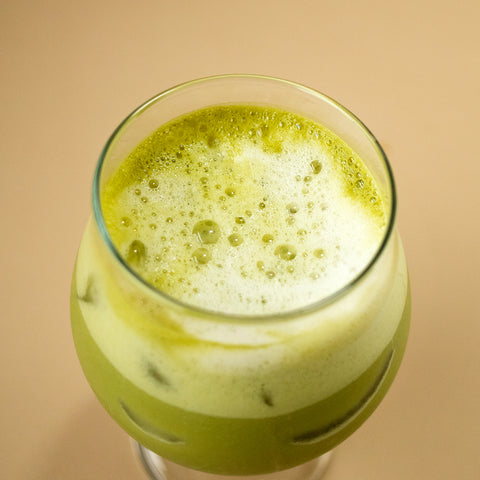Top view of an iced matcha latte in a beer glass.