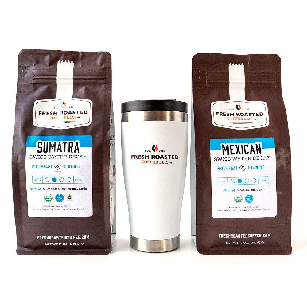 A bag of Organic Swiss Water Decaf Sumatra coffee, a bag of Organic Swiss Water Decaf Mexican coffee, and a white Fresh Roasted Coffee travel mug.