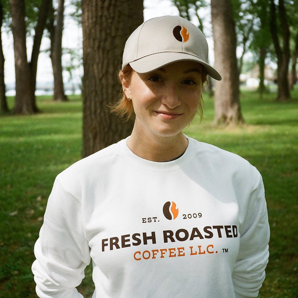 Woman wearing white Fresh Roasted Coffee sweatshirt and khaki hat with orange and black coffee bean logo.
