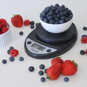 Black Escali Primo digital scale with a bowl of blueberries on top, surrounded by strawberries, blueberries, and raspberries.