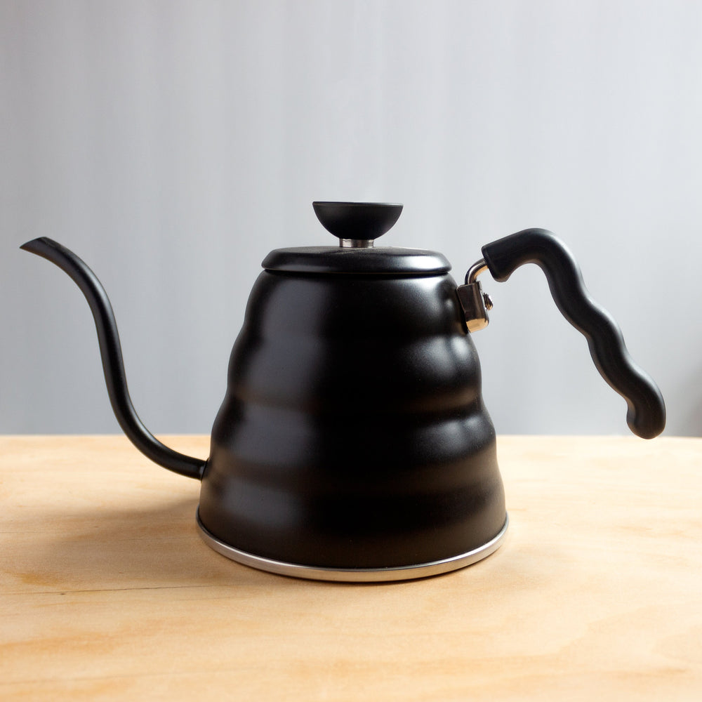Black Hario V60 Buono Coffee Drip Kettle on a table.