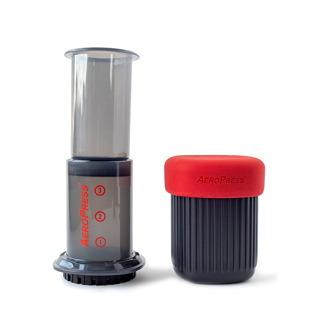 The AeroPress Go, a shorter, more packable version of the original AeroPress, next to its container with a red rubber top.
