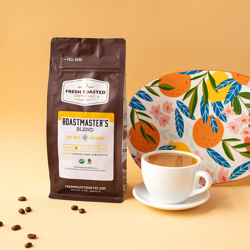Lifestyle photo of a bag of Roastmasters Blend coffee next to a cup of coffee.