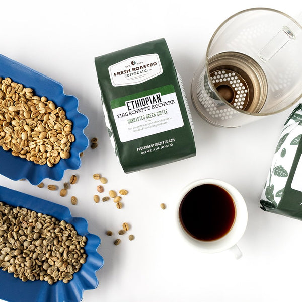 Green bag of unroasted Ethiopian Yirgacheffe Kochere coffee, bins of unroasted beans, clear roasting chamber, and a cup of coffee.