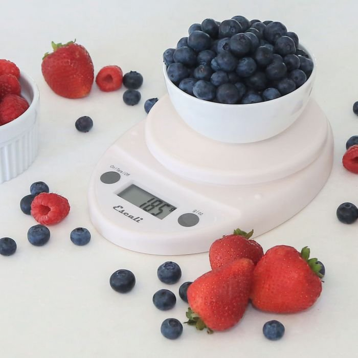 White Escali Primo digital scale with a bowl of blueberries on top, surrounded by strawberries, blueberries, and raspberries.