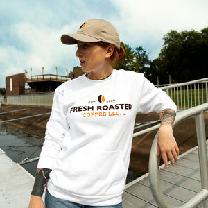 Woman, on a pier,  wearing white Fresh Roasted Coffee sweatshirt and khaki hat with orange and black coffee bean logo.
