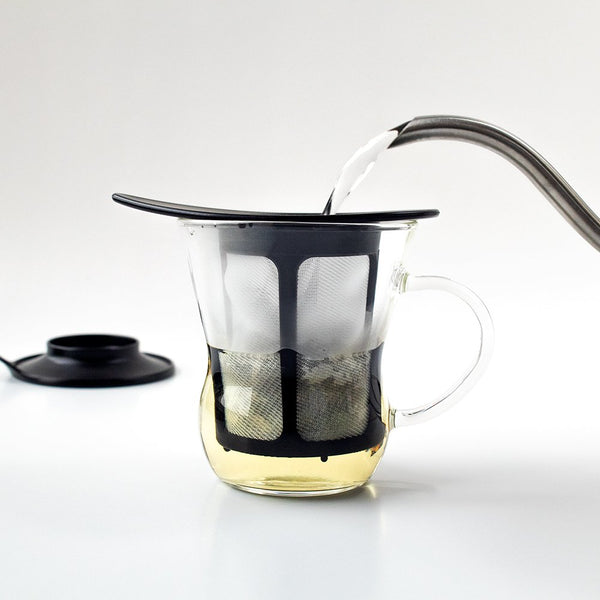 Spout pouring water into a Hario One Cup Tea Maker, lid in the background.